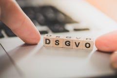 """DSGVO: Cubos de madeira com o  do """"DSGVO†das letras que encontra-se em um portátil Datenschutzgrundverordnung imagem de stock royalty free"""