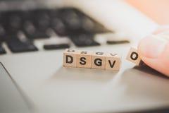 """DSGVO: Cubos de madeira com o  do """"DSGVO†das letras que encontra-se em um portátil Datenschutzgrundverordnung imagens de stock royalty free"""