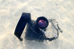 The DSLR camera fall to the sea water. Stock Photo