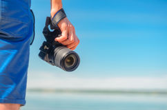 Dslr camera in a man`s hand close-up against a sea horizon. Dslr camera in the hand of a man standing on coast and looking for the story. Dslr camera in a man`s Royalty Free Stock Photo