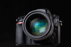 DSLR camera with lens. On black Royalty Free Stock Image