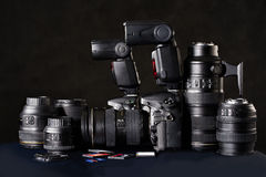 DSLR camera, lens and flash cards on black Royalty Free Stock Images
