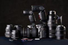 DSLR camera, lens and flash cards on black. Set of photographs. DSLR camera, lens and flash cards Royalty Free Stock Images