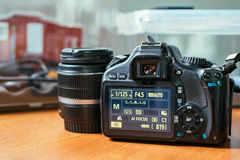 DSLR camera with lens on the wood table.  Stock Photography