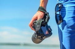 Dslr camera in a man`s hand close-up against a sea horizon. Dslr camera in the hand of a man standing on coast and looking for the story. Dslr camera in a man`s Royalty Free Stock Images