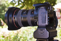 DSLR Camera - side profile with 17-20mm lens. Digital Single Lens Reflex Camera, with a short range wide angle zoom lens attached. Seen here with a battery stock image