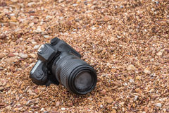 DSLR camera on stone beach wet from water sea wave. DSLR camera and tele lens wet from water sea wave at stone beach when travel and test using in the extreme Stock Photography