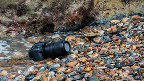DSLR camera on stone beach wet from water sea wave. DSLR camera and tele lens wet from water sea wave at stone beach when travel and test using in the extreme Royalty Free Stock Photo