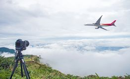 DSLR camera taking travel nature photography. full frame camera on tripod take photograph of airplane take off with beautiful lan. Dscape in background. DSLR stock photography