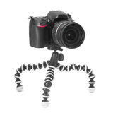 Dslr camera on tripod. Dslr camera on a small tripod isolated on white Royalty Free Stock Photo