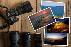 DSLR cyfrowa kamera, obiektyw, błysk i sterta fotografie na rocznika grunge drewnianym tle, Zdjęcie Royalty Free