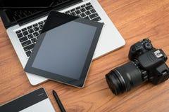 DSLR cyfrowa kamera z pastylki i notatnika laptopem zdjęcia stock