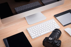 DSLR digital camera with tablet and computer PC. On wooden dask table Royalty Free Stock Image
