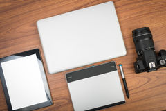 DSLR digital camera with tablet and notebook laptop. On wooden dask table Stock Photos