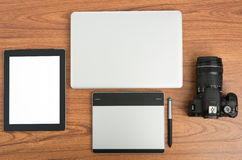 DSLR digital camera with tablet and notebook laptop. On wooden dask table Royalty Free Stock Image