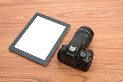 DSLR digital camera and tablet. On wooden dask table Royalty Free Stock Photography