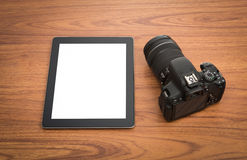 DSLR digital camera and tablet. On wooden dask table Stock Image