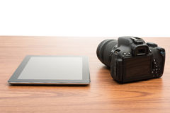 DSLR digital camera and tablet. On wooden dask table Royalty Free Stock Image