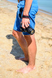 DSLR-Kamera in der Hand im Seestrandhintergrund Stockfoto