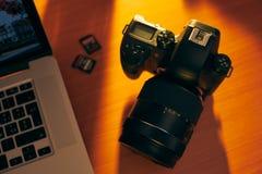 Dslr kamera och SDHC-minneskort på skrivbordet nära PC Royaltyfri Fotografi