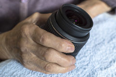 DSLR lens in old woman's hands. Royalty Free Stock Photography