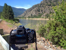 A DSLR Taking a Photo of a Wide Mountain River Royalty Free Stock Photo