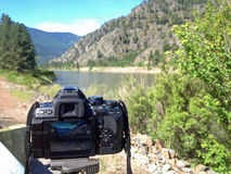 A DSLR Taking a Photo of a Wide Mountain River Stock Photography