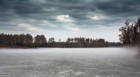 Düstere Landschaft auf dem gefrorenen nebelhaften See reif zwischen Winter und Frühling Lizenzfreie Stockfotografie