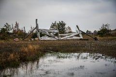 Düstere Landschaft mit altem gebrochenem hölzernem Zaun und Sumpf Lizenzfreie Stockfotos