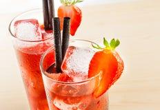 Détail de deux verres de cocktail de fraise avec de la glace sur la table en bois légère Image libre de droits