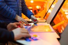 Détail sur des mains tenant des manettes et des manettes rouges et jouant un jeu dessus et la vieille arcade Photos stock
