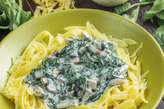Détail sur des pâtes avec des champignons d'épinards, de crème et de champignon de paris dessus Photographie stock libre de droits