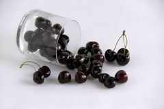 Cherries with overturned glass stock photo