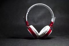 Duże przenośne i barwić słuchawki dla słuchać muzyka Biały i czerwony kolor Na monophonic czarnym tle obraz royalty free