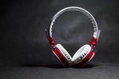 Duże przenośne i barwić słuchawki dla słuchać muzyka Biały i czerwony kolor Na monophonic czarnym tle obrazy stock