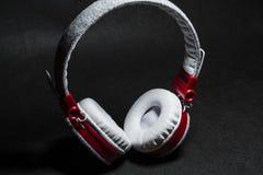 Duże przenośne i barwić słuchawki dla słuchać muzyka Biały i czerwony kolor Na monophonic czarnym tle zdjęcie royalty free