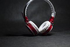 Duże przenośne i barwić słuchawki dla słuchać muzyka Biały i czerwony kolor Na monophonic czarnym tle zdjęcia stock