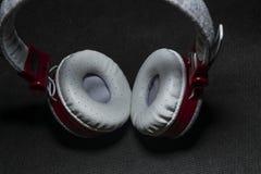 Duże przenośne i barwić słuchawki dla słuchać muzyka Biały i czerwony kolor Na monophonic czarnym tle fotografia stock