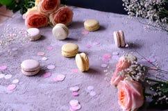 Dużo macaroons z bukietem piękne barwić róże obrazy stock