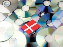 Duńska flaga na górze cd i DVD stosu odizolowywającego na bielu Obrazy Stock