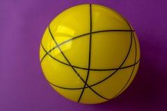 Duża żółta szklana piłka na fiołkowym tle Wciąż życie pasiasta żółta piłka na jaskrawym fiołka stole zdjęcia stock