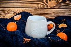 Duża biała filiżanka kakao na błękitnym trykotowym pulowerze z wibrującymi pomarańczowymi tangerines wokoło i anyży ziarnami przy zdjęcie stock