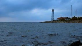 Duża biała latarnia morska na dennym brzeg przeciw tłu chmurny wieczór niebo zbiory