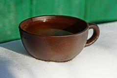 Duża brown filiżanka z wodą na śniegu Fotografia Stock