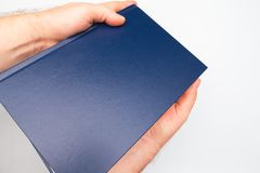 Duża ciężka błękitna książka w rękach obrazy royalty free