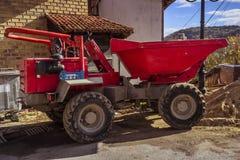 Duża czerwona usyp ciężarówka przed budynkiem w budowie zdjęcia stock
