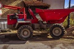 Duża czerwona usyp ciężarówka przed budynkiem w budowie obraz stock