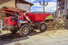 Duża czerwona usyp ciężarówka przed budynkiem w budowie obrazy stock