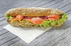 Duża i serdecznie kanapka z, łososiem polędwicowym, sałatkowym, pojęcie lunch na drewnianym szarym backg zdjęcie royalty free