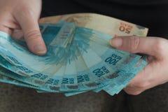 Duża kwota brazylijski pieniądze, reais, w ręce, pojęcie sukces zdjęcie stock